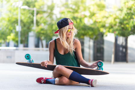 attractive young pensive woman who is wearing casual clothes, sitting on the ground and holding a skateboard