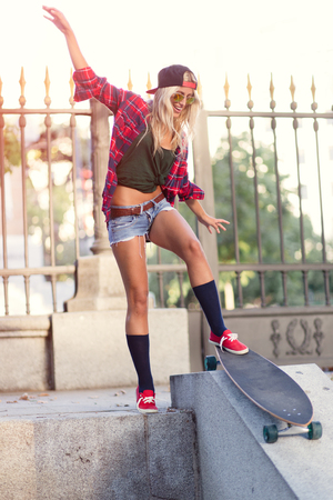 attractive young cheerful woman skating in the street on a sunny day in summer
