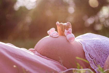 cerca de los zapatos de bebé en un vientre embarazado al aire libre