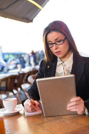 Focused businesswoman working taking notes while looking at a tablet computer sitting at a cafe terrace