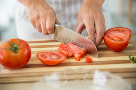 gazpacho: anonymous chef chopping tomatoes for preparing a gazpacho, spanish traditional cold soup