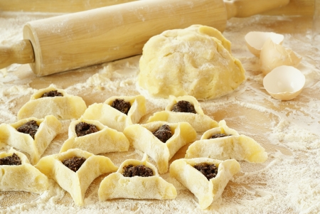 Preparing cookies with poppy seed filling for Purim (Hamantaschen)                   Stockfoto