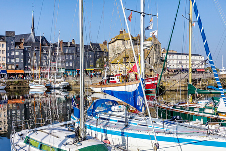 Picturesque and quaint old harbor at the Normandy village of Honfleur France with boats, sailboats, cafes and the sea on a sunny summer day
