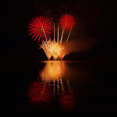 murky: Red and golden fireworks reflected in a murky lake