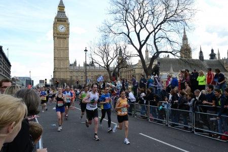 London, United Kingdom - April 22, 2012: Runners participating in the London Marathon 2012 passing The Houses of Parliament and Big Ben