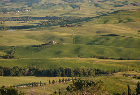 Panoramic view on farmland in Tuscan landscape as the sun sets photo