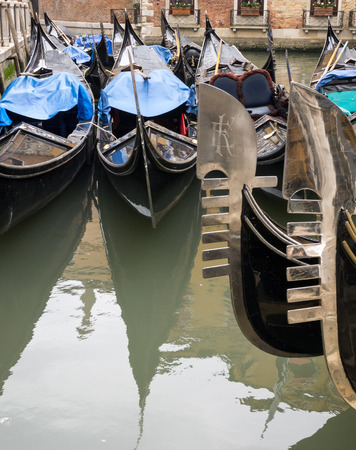 ferro: The shining six-toothed ferro pieces on the prows of a number of Venetian gondalas and two more gondolas in the background Stock Photo
