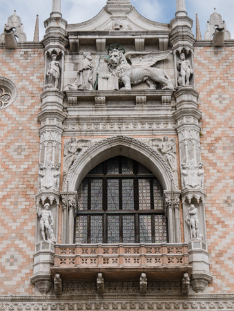 doge's palace: Sculpture of the Doge kneeling in front of the winged lion at Doges Palace west facade in Venice Stock Photo