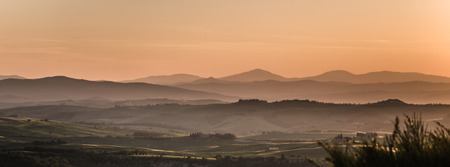 Panoramic view on fields in Tuscan landscape colored by the setting sun with clear silhouette of the mountains in the background photo