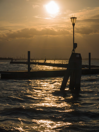 bollards: Sunset over the lagoon of Venice with bollards appearing as silhouettes Stock Photo