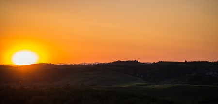 Panoramic view on Tuscan landscape colored by the setting sun with clear silhouettes of cypress trees and the mountains in the background photo