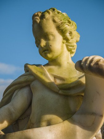 Cherub in the garden of Soestdijk Palace in the Netherlands holding a scroll
