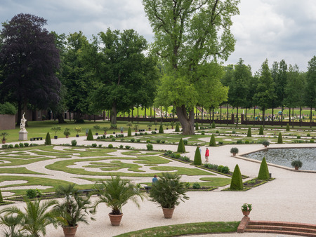 family owned: APELDOORN, NETHERLANDS - JUNE 14: View on palace Het Loo with visitors in the gardens on June 14, 2013. The palace, which houses a museum,  was built in the 17th century and is one of the palaces still owned by the Dutch royal family.