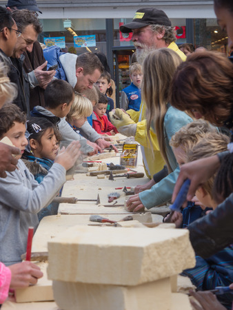hand carved: ALMERE, NETHERLANDS - OCT. 26: Children attending a workhop marl stone carving at the annual Sculpture Festival being held in the townsquare of Almere on June 26, 2013 Editorial