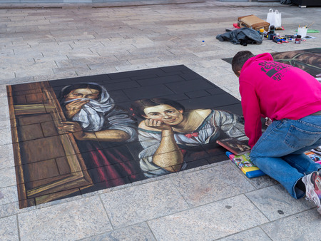 ALMERE, NETHERLANDS - JUNE 30: Artist at work on a street painting during the annual Steet Art Festival held in the streets of the city of Almere on June 30, 2013