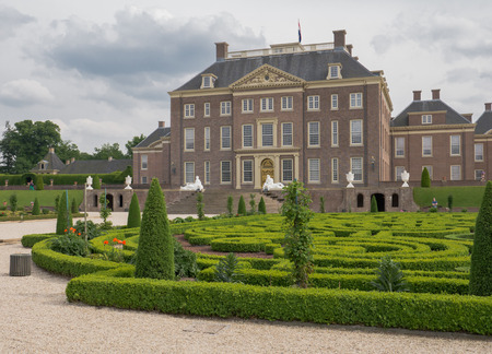 APELDOORN, NETHERLANDS - JUNE 14: View on palace Het Loo with visitors in the gardens on June 14, 2013. The palace, which houses a museum,  was built in the 17th century and is one of the palaces still owned by the Dutch royal family.