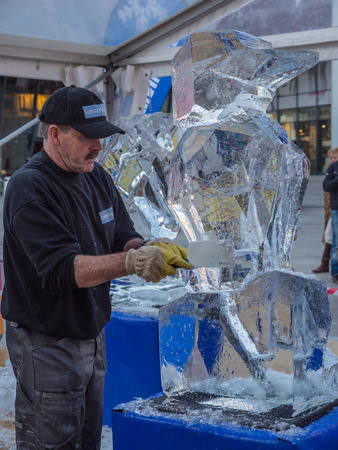 hand carved: ALMERE, NETHERLANDS - OCT. 26: Ice sculptor at work during the annual Sculpture Festival being held in the townsquare of Almere on June 26, 2013
