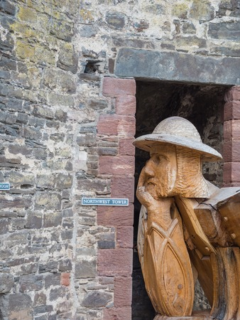 king edward: Wooden soldier at the entrance of massive Conwy Castle in Wales built by king Edward I as one of the fortifications during the conquest of Wales in the 13th Century Stock Photo