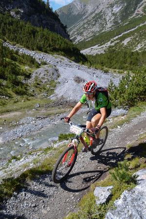 GRAUBUNDEN, SWITZERLAND - 20 AUGUST 2012:  Unidentified mountain biker taking part in the yearly held multi-day recreational mountain bike tour called 'Mountain Rally' in Switzerland in the summer 2012