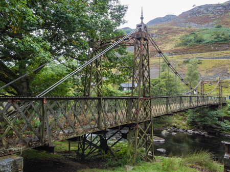 elan: Old out of use metal suspension bridge crossing a river in the Elan Valley, Wales, overgrown by plants