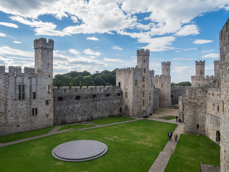 CAERNARFON, WALES - 29 SEPTEMBER 2013: View on the inner courtyard at Caernarfon Castle, well-known for its polygonal towers.   In 1969 Prince Charles was invested here as Prince of Wales by HM Queen Elizabeth II.