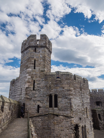 norman castle: CAERNARFON, WALES - 29 SEPTEMBER 2013: One of the polygonal towers of Caernarfon Castle from the 13th century. In 1969 Prince Charles was invested here as Prince of Wales by HM Queen Elizabeth II.