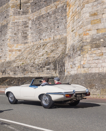 CAERNARFON, WALES - 29 SEPTEMBER 2013: Vintage classic car taking part in the Walled Towns Trail Car Run 2013 passes the walls of Caernarfon Castle en route to its next destination