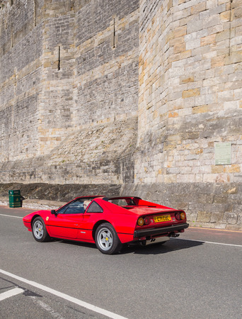 CAERNARFON, WALES - 29 SEPTEMBER 2013: Vintage classic Ferrari car taking part in the Walled Towns Trail Car Run 2013 passes the walls of Caernarfon Castle en route to its next destination