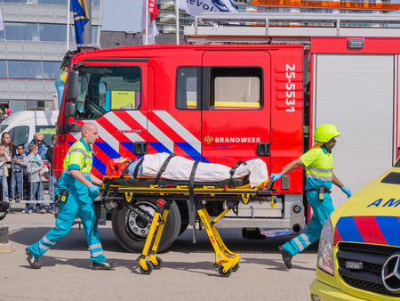 ALMERE, NETHERLANDS - 12 APRIL 2014: Firefighters and medical services at work in an enacted emergency scene during the first National Security Day held in the city of Almere