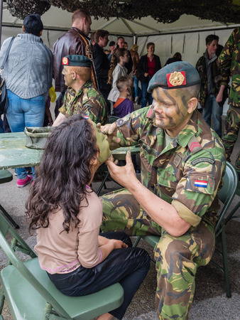 concealment: ALMERE, NETHERLANDS - 12 APRIL 2014: Kids get camouflage make-up painted on their faces by the military on National Army Day  in the city of Almere