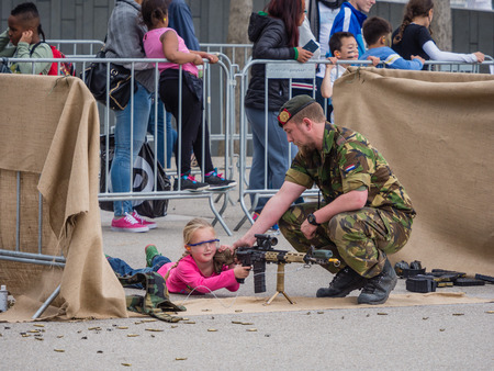weaponry: ALMERE, NETHERLANDS - 23 APRIL 2014: On National Army Day kids of all ages  are allowed to try out weaponry with dumy bullets under guidance of the military in Almere Editorial