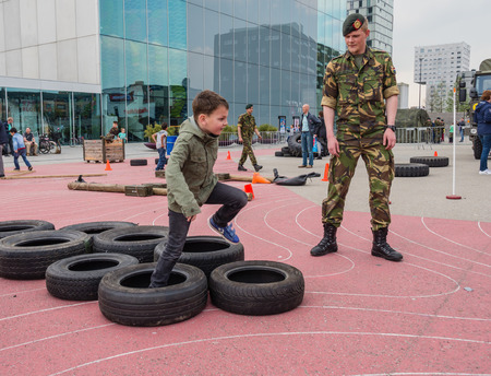 make public: ALMERE, NETHERLANDS - 23 APRIL 2014: Children run part of a military assault course on National Army Day meant to make the public acquainted with the army