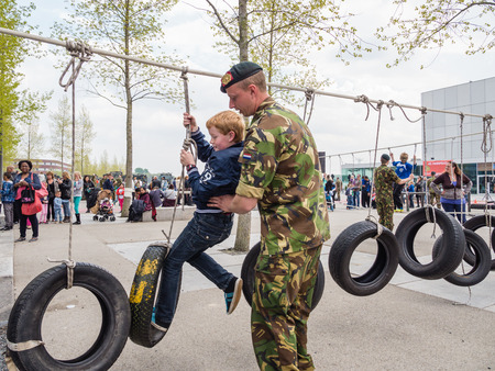 make public: ALMERE, NETHERLANDS - 23 APRIL 2014: Children battling part of a military assault course on National Army Day meant to make the public acquainted with the army