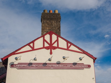longest: The longest place name of the UK, Llanfairpwllgwyngyll, on one of the public buildings in the town Stock Photo