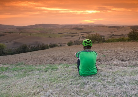 mountain biker: Mountain biker resting after a ride in Tuscan landscape as the sun sets Stock Photo