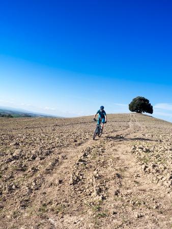 mountain biker: Mountain biker riding  a trail in a Tuscan landscape near Siena, Italy
