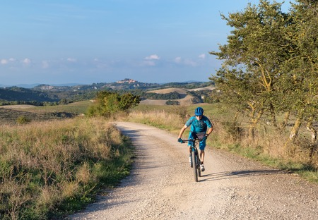 Mountain biker riding  a trail in a Tuscan landscape near Siena, Italy