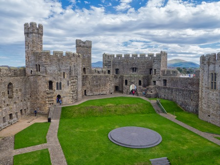 CAERNARFON, WALES - 29 SEPT. 2013: View on Caernarfon Castle with visitors in the courtyard. The castle is a major landmark in Wales and attracts thousands of tourists each year