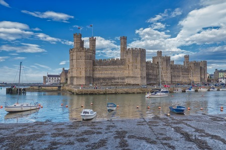 castle: CAERNARFON, WALES - 29 SEPT. 2013: View on Caernarfon Castle with boats moored in the Seiont river. The castle is a major landmark in Wales and attracts thousands of tourists each year