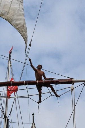 topsail: AMSTERDAM - 21 AUGUST 2015: Sailor climbs the mast of topsail schooner Bel Espoir which is moored in the port of Amsterdam for Sail 2015. Sail is held every five years and attracts two million visitors