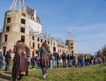 almere: ALMERE, NETHERLANDS - 31 OCT. 2015: People wait in line to visit the abandoned and unfinished castle of Almere. The modern ruin and grounds will be transformed into a theme park which opens in 2019