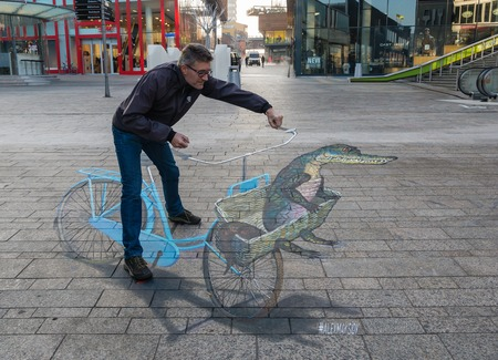 ALMERE, NETHERLANDS - 27 OCT. 2015: Man showing the power of 3D optical illusion on a street painting of a bicycle in the city of Almere Editorial