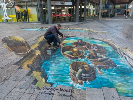 street painting: ALMERE, NETHERLANDS - 27 OCT. 2015: Man showing the power of 3D optical illusion on a street painting of men in wooden tubs in the city of Almere