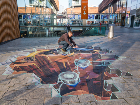 ALMERE, NETHERLANDS - 27 OCT. 2015: Man showing the power of 3D optical illusion on a street painting of a crater in the earth's crustal in the city of Almere