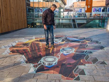 Almere, Holandia - 27 października 2015: Nieznany mężczyzna pokazuje moc 3D iluzji optycznej obrazu ulicy przez nieznanego artystę. Raz w roku miasto pozwala artystów, aby obrazy na ulicach Publikacyjne