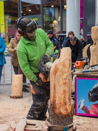 talla en madera: Almere, Holanda - el 27 de-OCT-. 2015: Talla de madera artista en el trabajo en el townsquare de Almere hace una escultura. Una vez al año se reúnen artistas de la calle para mostrar sus habilidades al público en la ciudad.