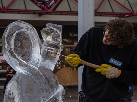 public figure: ALMERE, NETHERLANDS - 27 OCT. 2015: Ice sculptor in the townsquare of Almere. sculpts a figure. Once a year street artists gather to show of their skills to the public in the city. Editorial