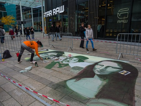 ALMERE, NETHERLANDS - 27 OCT. 2015:  Unknown artist at work on street painting that shows the power of 3D optical illusion. Once a year the city of Almere allows artists to create street art