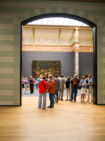 rembrandt: AMSTERDAM - 2 JULY 2014:Tourists in one of the rooms of national Rijksmuseum, a popular destination for tourists. In the background people look at the famous Nightwatch painting by Rembrandt Editorial