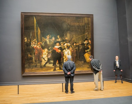 rembrandt: AMSTERDAM - 2 JULY 2014: Tourists in one of the rooms of national Rijksmuseum scrutinize the world famous Nightwatch painting by Rembrandt. The musuem attracts more than 2 million visitors each year